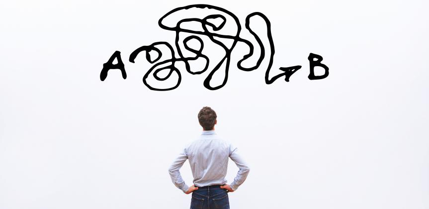 The back of a man looking at a white board with a big scribble black line between points A and B