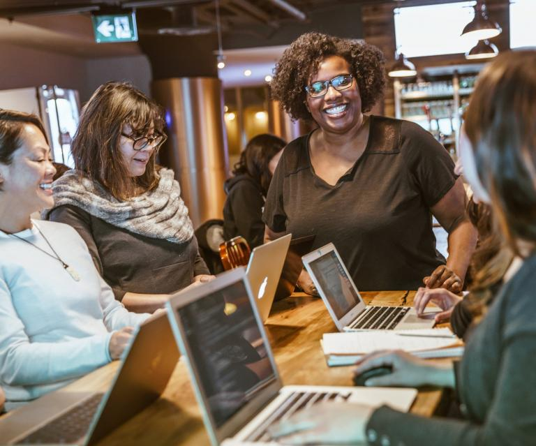 Smiling people at an office table working on laptops