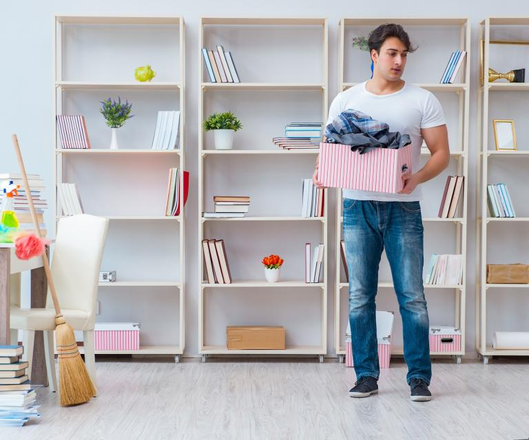 A man with a box of clothes and cleaning up shelves